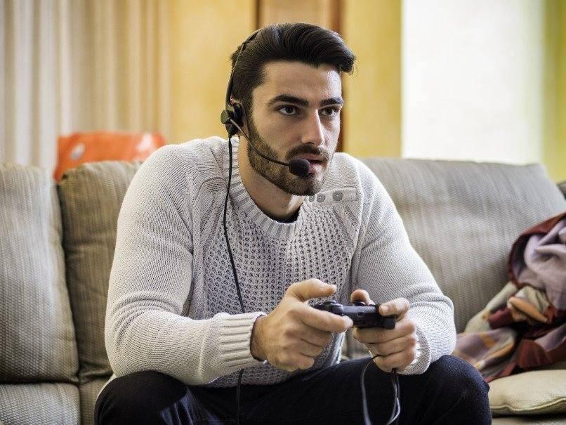 άντρας παίζει παιχνίδι με κονσόλα και ακουστικά